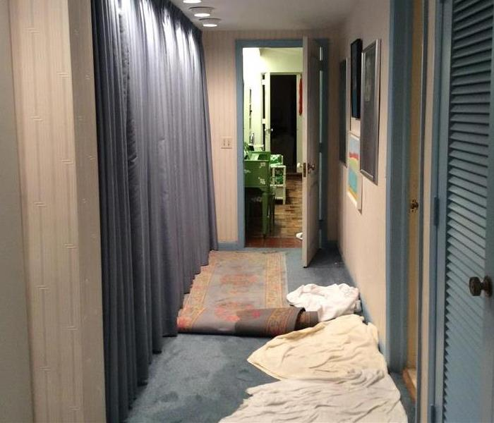 Hallway with wet carpet and towels on the floor.