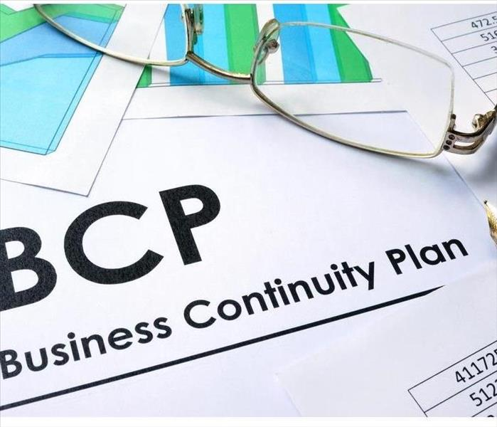 Business Continuity Plan sheet with eyeglasses and pen